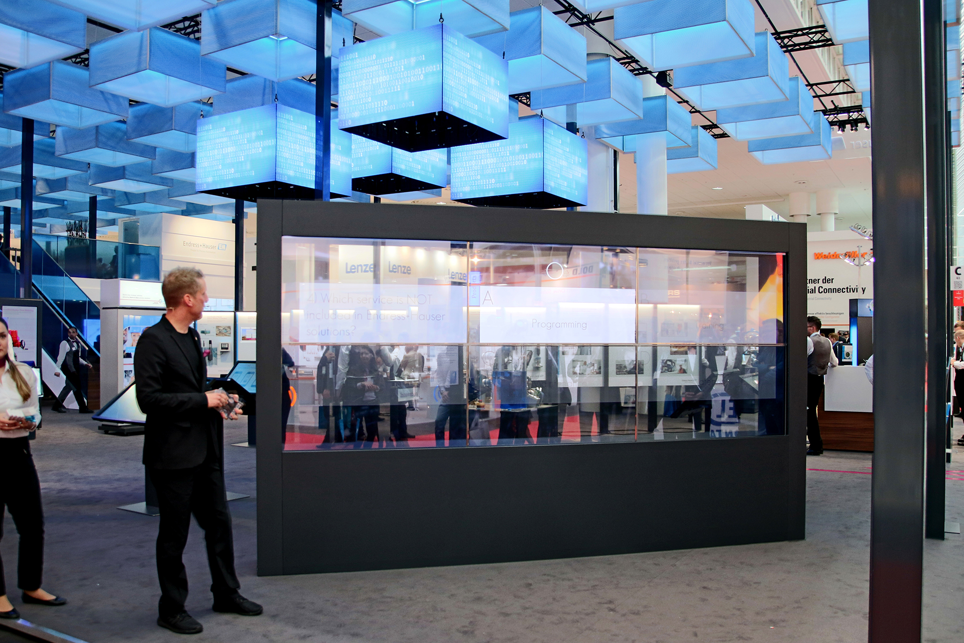 The visual effect of the transparent OLED Powerwall combined with the interplay of produced content and the moderated live presentation creates great amazement among visitors. Depending on the theme, colorful liquids spill into the screens or out again via an animation. Presented texts are partly superimposed and flow together with the liquid.