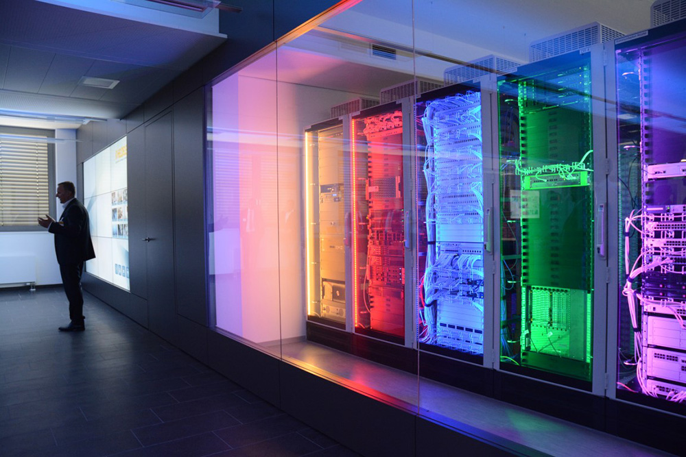 Modern technology, usually rather installed in the basement of a company, is impressively staged in the showroom. Here, control cabinets are illuminated in colour depending on the respective presentation topic, in order to visually clarify the connections between virtual content and real hardware to interested customers. A classic media control forms the interface between the smartPerform presentation interface and the light and room control.