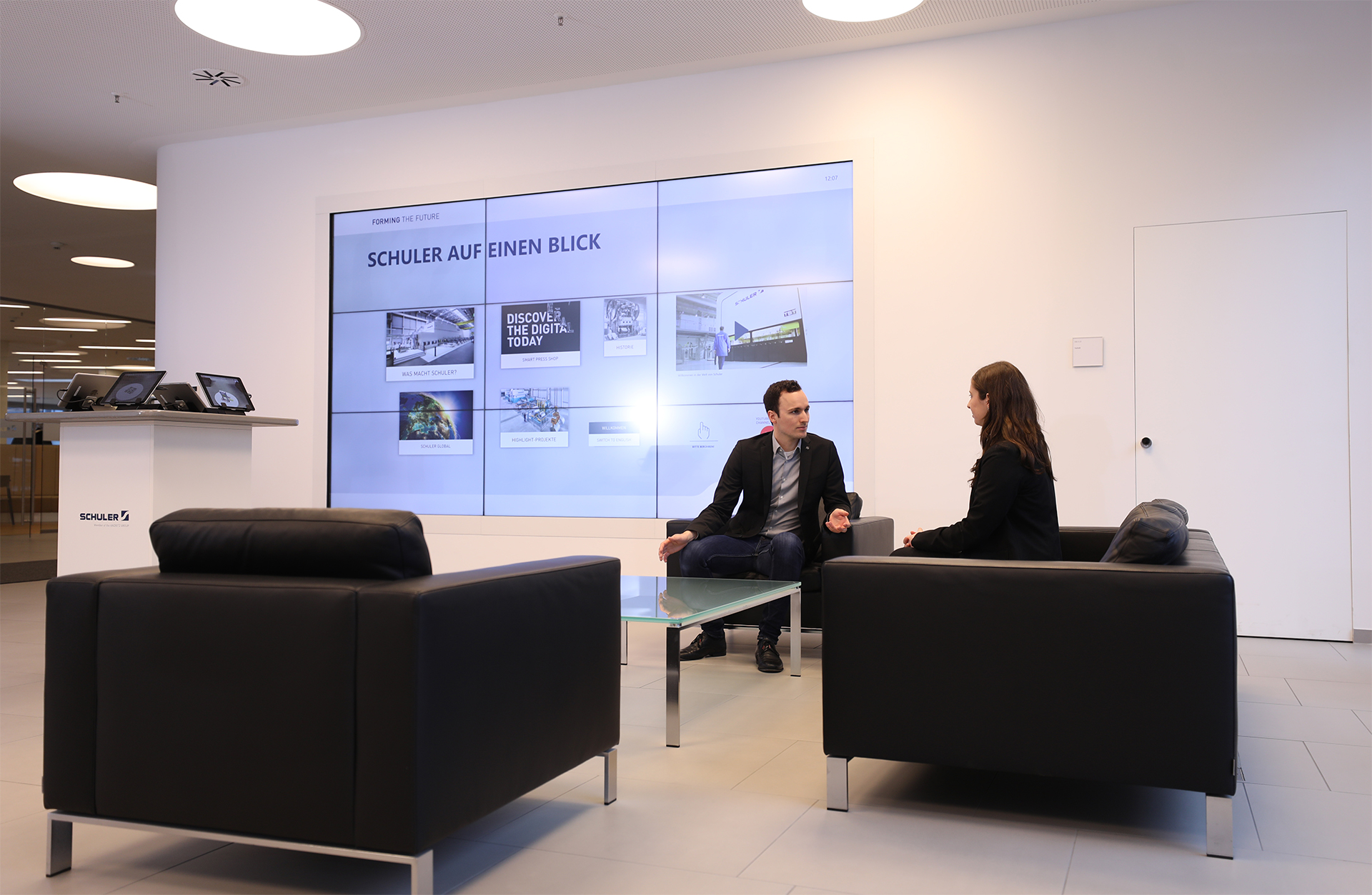 In the entrance area, a seating area invites you to spend some time with colleagues or visitors. An impressive large screen in the form of an interactive multi-touch Powerwall stages the Schuler brand and its products there. Tailor-made user interfaces powered by smartPerform inform about the company's considerable history, show examples of applications in the various market segments or provide a glimpse of highlight projects.