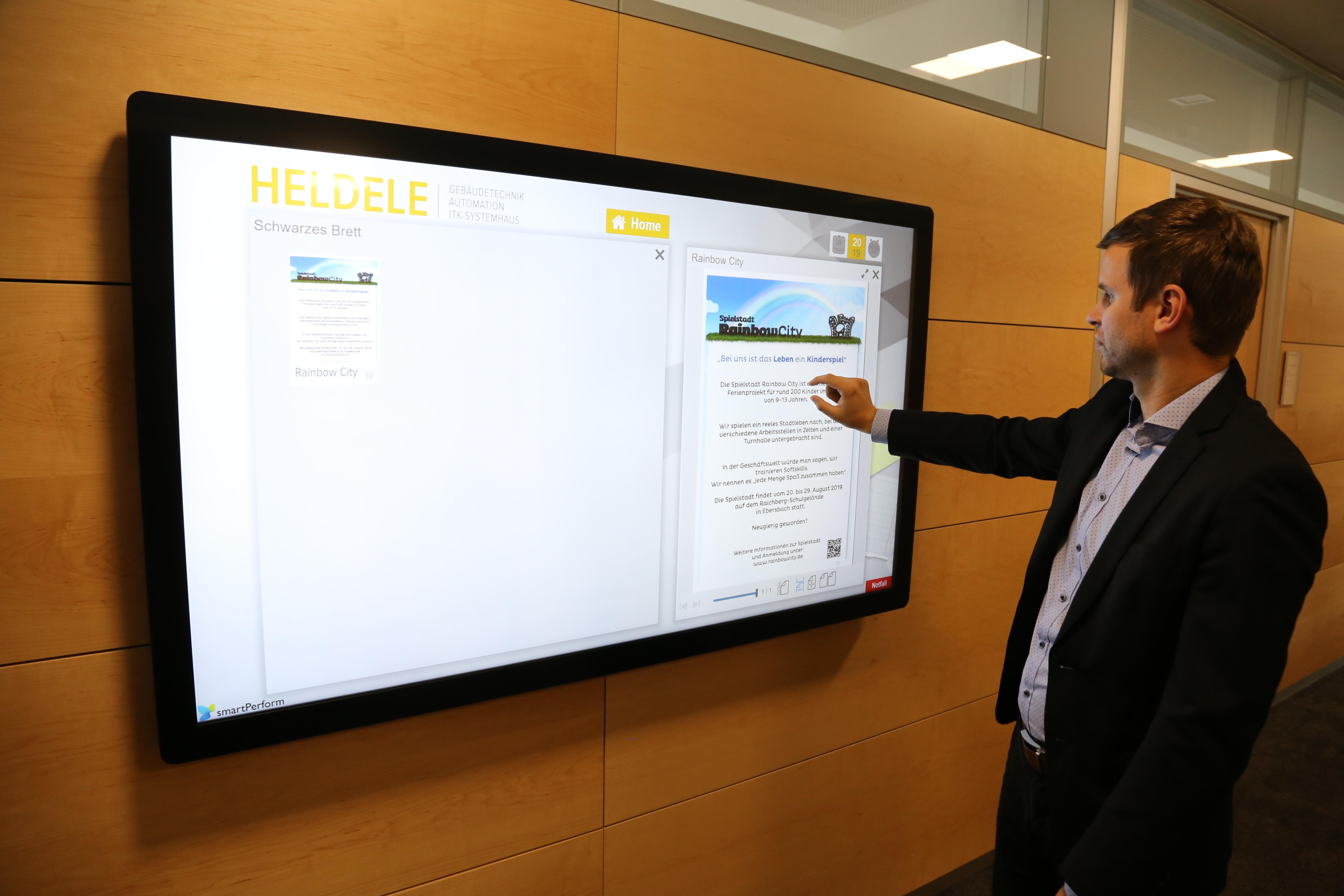 Im Eingangsbereich lädt eine Sitzecke zum Verweilen ein. Ein beeindruckender Großbildschirm in Form einer interaktiven Multi-Touch Powerwall inszeniert dort die Marke Schuler und deren Produkte.
